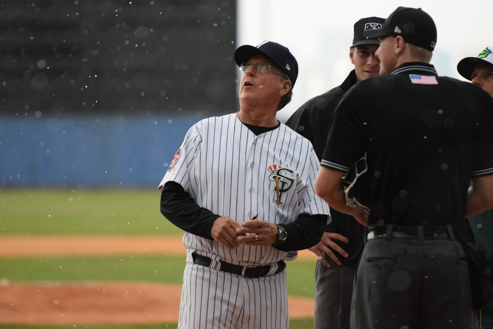 Rain was coming down during the pre-game manager's meeting at the plate. (Robert M. Pimpsner)